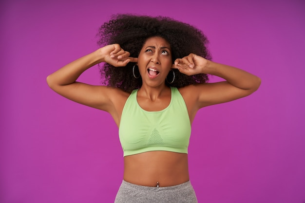 Portrait of young dark skinned woman with curls wearing casual hairstyle, standing on purple in light green top, coning ears and looking upwards with pout