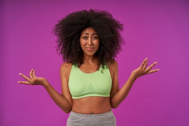 Ritratto di giovane donna dalla pelle scura con capelli ricci che indossa un top verde chiaro, in piedi sul viola con i palmi sollevati, fronte accigliata e rugosa con le labbra piegate