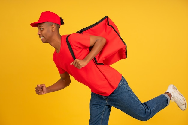 Portrait of young delivery man dressed in a red uniform running over isolated background. delivery concept.