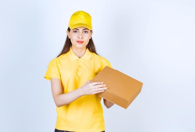 Ritratto di giovane fattorina che tiene singola scatola su bianco.