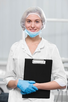 Portrait of young dentist holding clipboard