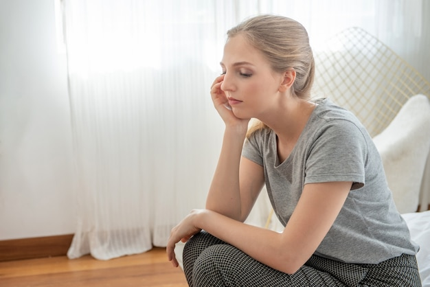 Portrait of young depressed caucasian woman dress in casual dress sit on bed with sorrow,hopeless,unhappy in trouble emotion.