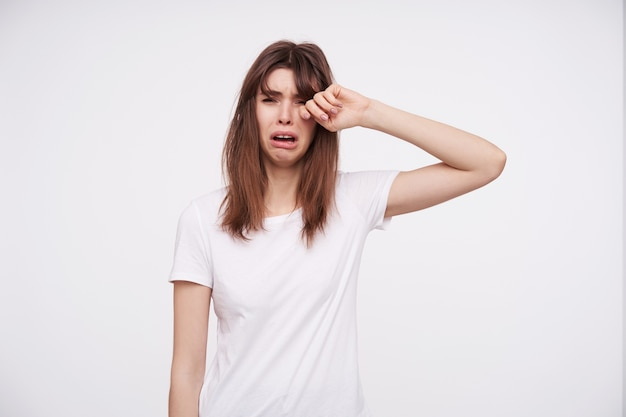 Portrait of young depressed dark haired female rubbing her eye with raised hand and twisting her lips while crying, wearing casual clothes while posing over white wall