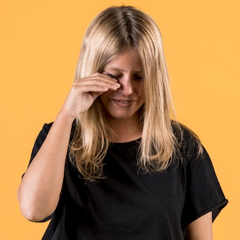 Portrait of young disable woman crying on plain backdrop