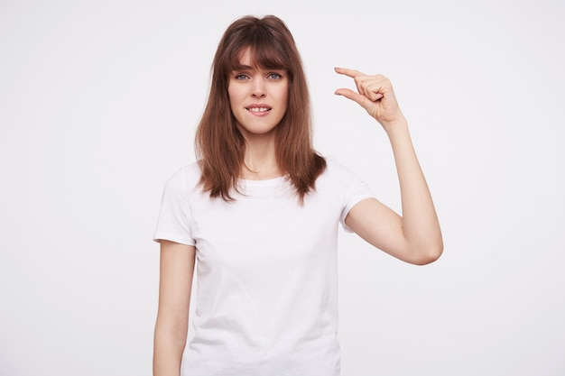 Portrait of young disappointed attractive brunette female with casual hairstyle showing small size with her fingers and biting underlip while looking , isolated over white wall