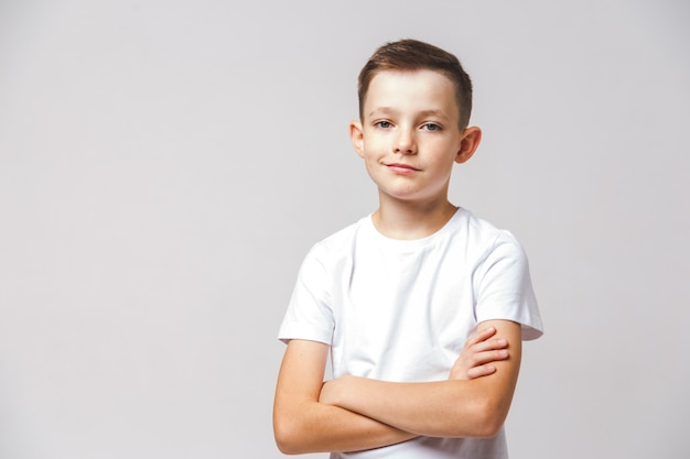 Portrait of young displeased boy with cross arms on white background