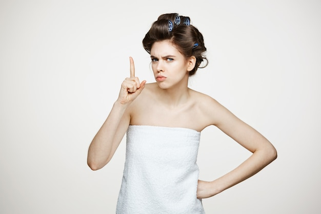 Portrait of young displeased woman in hair curlers. beauty cosmetology and spa.