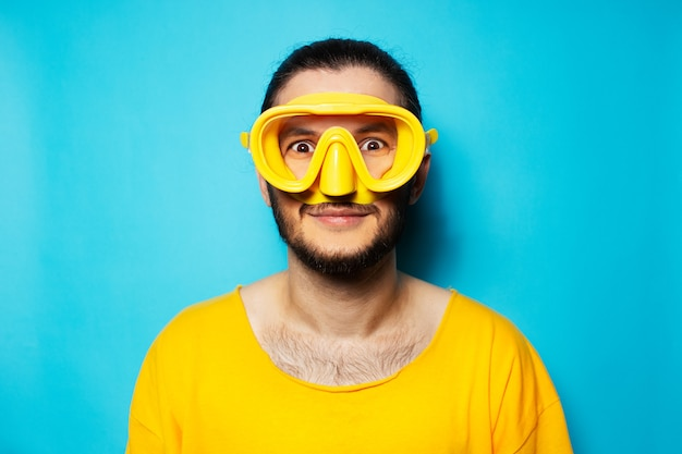 Portrait of young diving man wearing yellow googles for swim on blue background.
