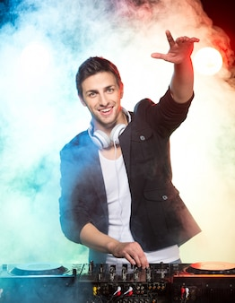 Portrait of a young dj with mixer on foggy