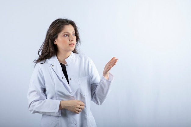 Portrait of young doctor looking at something on white wall.
