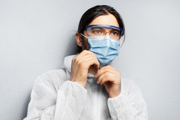 Portrait of young doctor man wearing ppe suit, putting on medical face mask against coronavirus and covid-19.