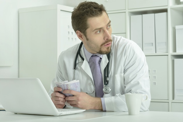 Portrait of young doctor with laptop and money