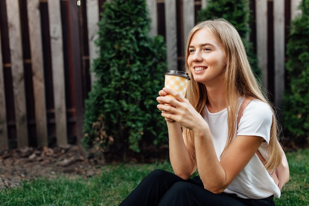 Portrait of a young, dressed in a white t-shirt, outdoors. girl sitting on the lawn and drinking coffee.