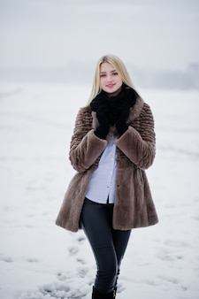 Portrait of young elegance blonde woman in a fur coat, foggy river on winter ice.