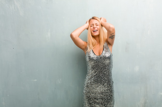 Portrait of young elegant blonde woman crazy and desperate, screaming out of control