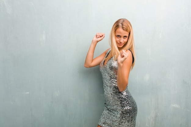 Portrait of young elegant blonde woman listening to music, dancing and having fun.