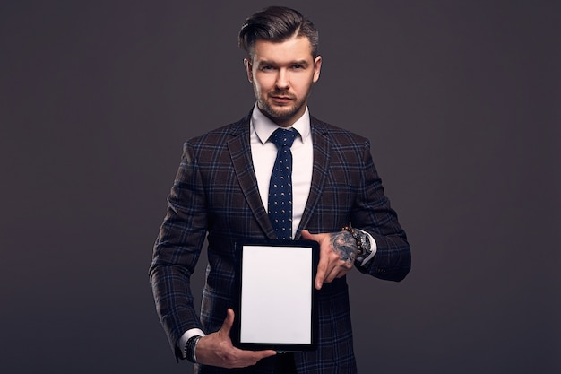 Portrait of a young elegant brutal man with tablet