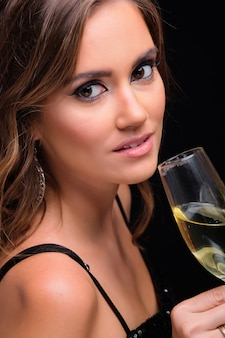 Portrait of young elegant woman drinking champagne against black