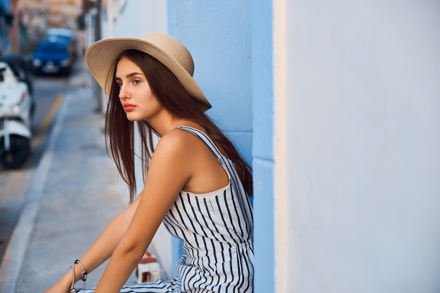 Portrait of young elegant woman in straw hat sitting on the street.