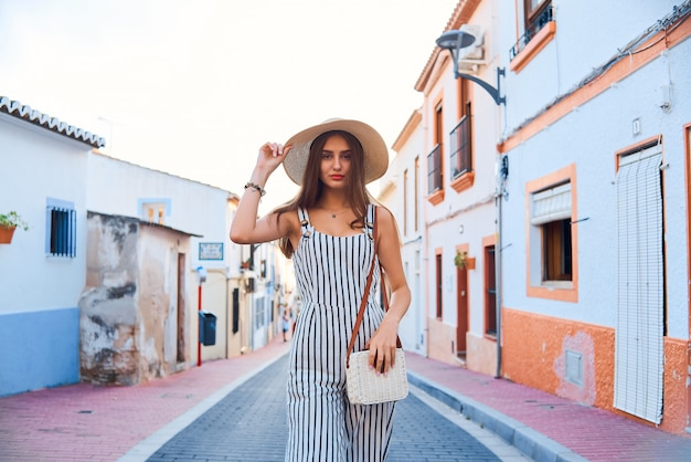 Portrait of young elegant woman in straw hat walking on the narrow streets of the old town.