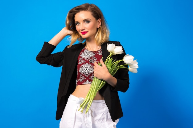 Portrait of young elegant woman with bright make up and dark blazer, holding white flowers
