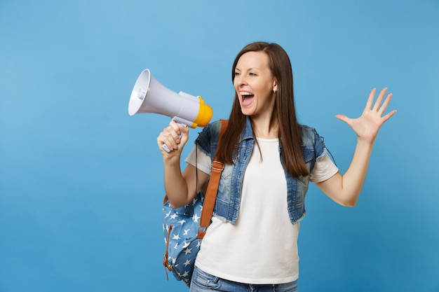 Portrait of young emotional woman student in denim clothes with backpack hold megaphone screaming spreading hands isolated on blue background. education in high school. copy space for advertisement.