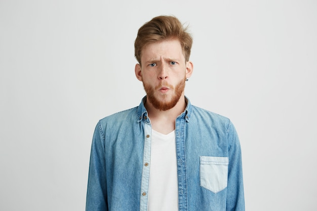 Portrait of young emotive shocked man frowning looking at camera.