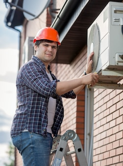 Portrait of young engineer installing air conditioner on building outer wall