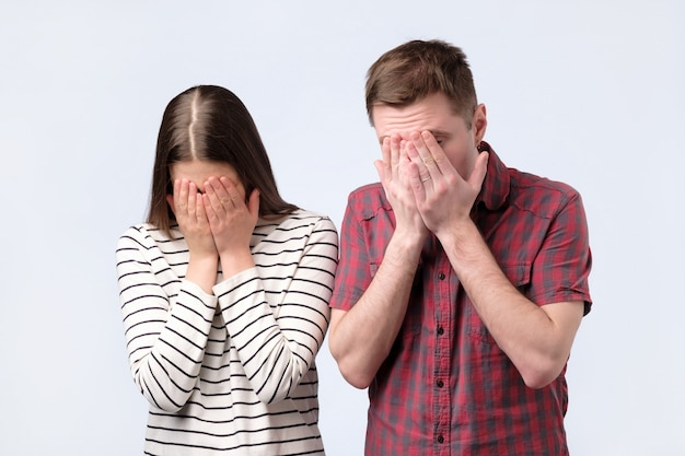 Portrait of a young european couple covering face with hands