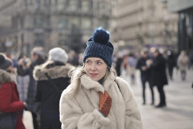 Ritratto di una giovane donna europea con una pelliccia e un cappello all'aperto