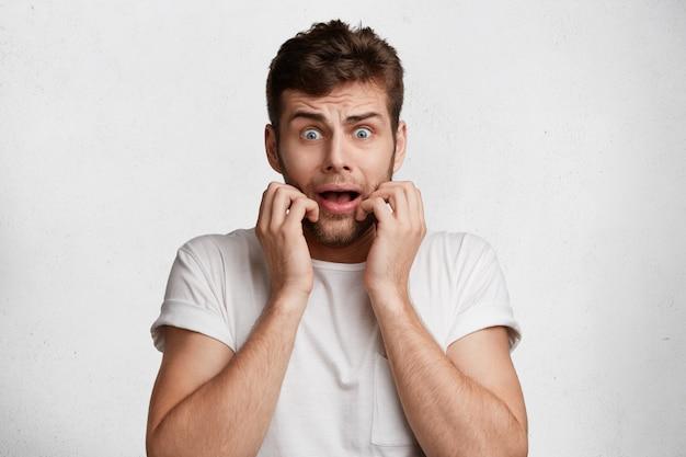 Ritratto di giovane uomo europeo in stato di stupore mentre vede la sua fobia, tiene la bocca aperta, esprime paura,