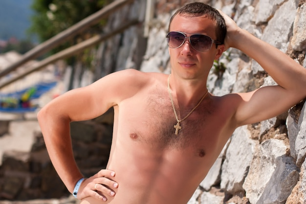 Portrait a young european man in swimsuit and sunglasses sunbathing outdoors in sunny day.