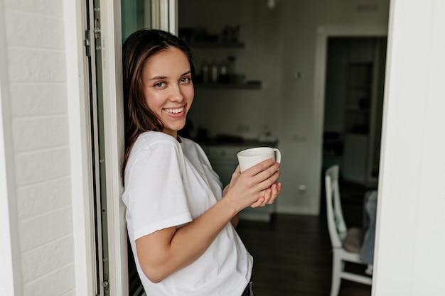 Ritratto di giovane donna europea con capelli scuri e pelle sana sorridente con il caffè del mattino nella moderna cucina leggera.