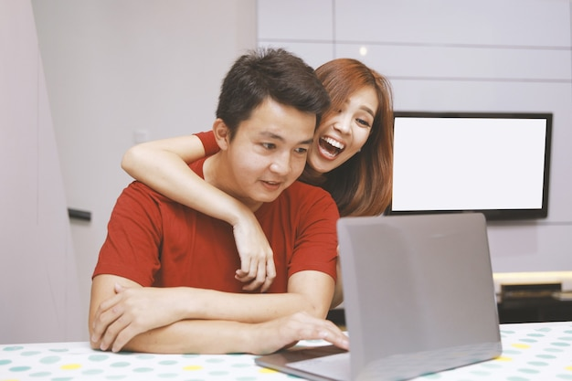 Portrait of young excited asian couple hugging while working with laptop at home with white interior on the background