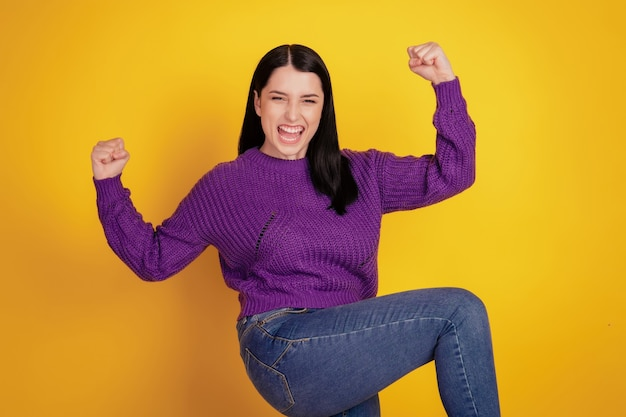 Portrait of young excited girl fists up crejoice win victory success lucky sale isolated over yellov color background