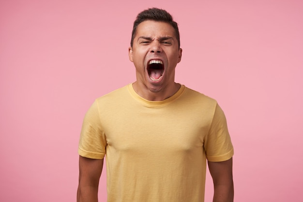 Portrait of young excited short haired man with short haircut frowning his face while screaming madly, standing against pink background with hands down