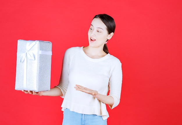 Portrait of young excited woman holding gift box and point hand on it
