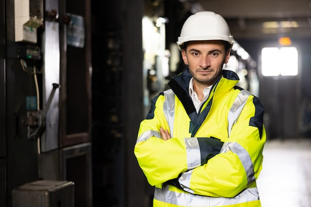 Portrait of young factory engineer or worker wearing safety vest and hard hat crossing arms