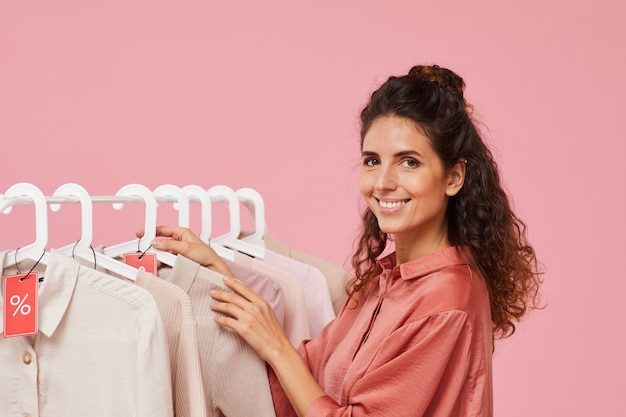 Portrait of young fashion designer smiling at camera while standing near the rack with clothes