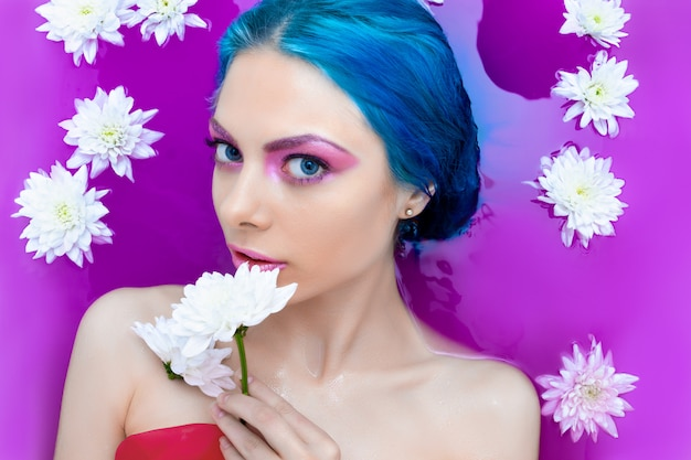Portrait of young fashion luxury sexy woman with blue hair relaxing in bathtub.