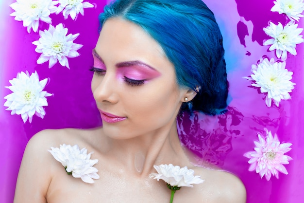 Portrait of young fashion woman with blue hair relaxing in bathtub.