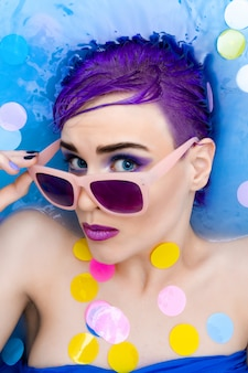 Portrait of young fashion woman with purple hair and makeup relaxing in bath.