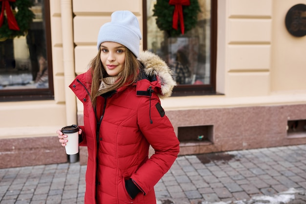 Portrait of a young fashionable girl walking on the street of the city in winter time