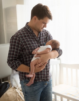 Portrait of young father holding newborn baby on hands at home