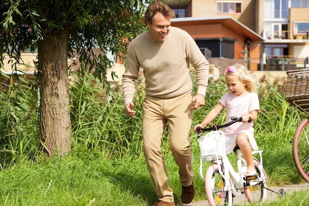 Portrait of young father teaching her daughter cycling in the park