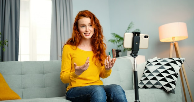 Portrait of young female blogger sitting on couch and talking in front of smartphone webcam
