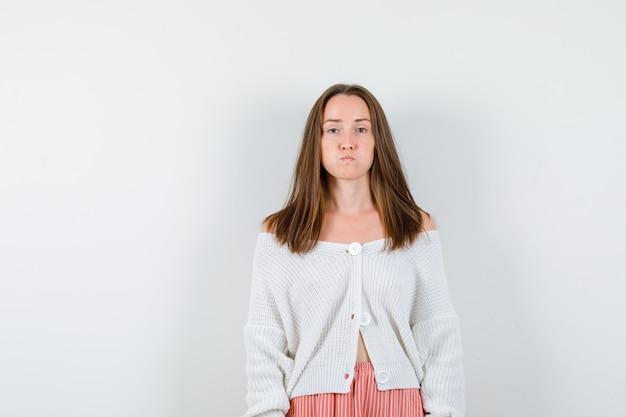 Ritratto di giovane donna che soffia guance in cardigan e gonna annoiata isolato