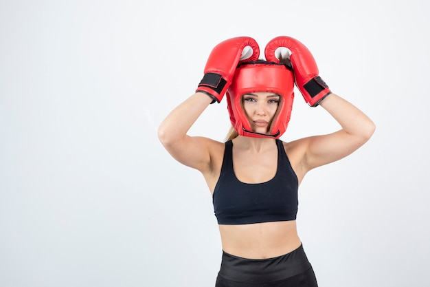 Portrait of young female boxer in red gloves and helmet fighting.