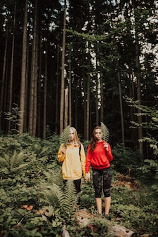 Portrait  of young female couple holding hands in the forest.