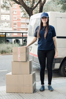 Portrait of a young female courier standing with stacked cardboard boxes